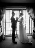 Black and white photo of newlyweds posing against window Royalty Free Stock Photo