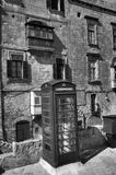 A black and white photo of an old cardphone booth in the historic city Valletta with an old appartment building in the background Stock Photography