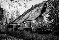 Black-white photo of old cozy house with thatched roof Stock Photo