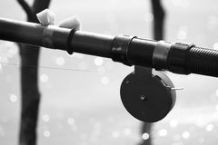 Black-and-white photo with old fishing rod in retro style close-up against the backdrop of lake and bokeh Royalty Free Stock Photos