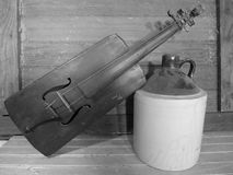 Handmade fiddle and moonshine jug black and white stock photo