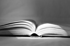 Black and white photo with an open book, the front part of which is lit by a ray of sun. Stock Photography