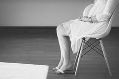 Black and white photo of pregnant female sitting Royalty Free Stock Images