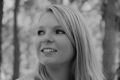 Black and white photo of the profile of a smiling woman`s face.  royalty free stock photo
