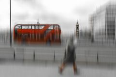 Black and white photo with red double decker bus in London. Red double decker bus and people on tre street, surrounded by the black and white city. Motion blur Stock Photo