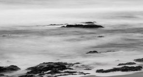 Black and white photo of rocks in the sea. Waves flowing over rocks in the sea Royalty Free Stock Photos