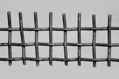 Black and white photo rusty metal fence on a grey background.  Royalty Free Stock Image