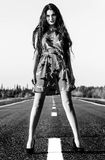 Black and white photo of a sexy woman staying on the road Stock Image