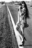 Black and white photo of a sexy woman staying on the road Royalty Free Stock Photography