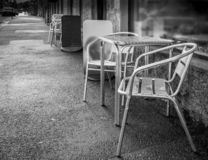 Black and white photo of silver chrome non corrosive chairs with matching table. Sitting outside on street pavement outside shop window front stock photos