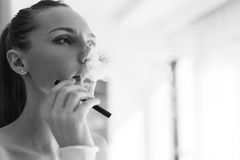 Black-white photo of smoking girl. Black and white photo of smoking girl indoors stock photo