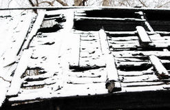 Black and white photo snowy abandoned burned-out fire wooden house. Stock Photos