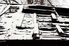 Black and white photo snowy abandoned burned-out fire wooden house. Royalty Free Stock Photography