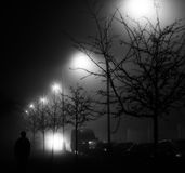 A black and white photo of a street at night with street lights shining behind the trees and silhouette of a person. On a foggy night Royalty Free Stock Image