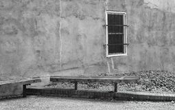 An old rustic alley wall with one solitary barred window. royalty free stock images