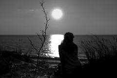 Black the white photo of a sunset at the sea. With a silhouette of the person royalty free stock photo