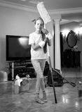 Black and white photo of teenager girl cleaning house with swab Royalty Free Stock Image