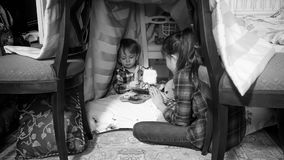 Black and white photo of toddler boy with sister reading book in tent at bedroom. Monochrome photo of toddler boy with sister reading book in tent at bedroom Stock Photos