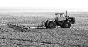 Black-and-white photo of tractor in field Stock Images