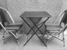 Black and white photo of two cafe chairs and table outdoors royalty free stock photo