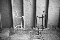 Black and white photo of two chairs facing each other in loft space. minimal concept. stock image