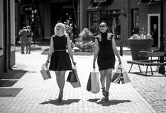 Black and white photo of two women walking with shopping bags Stock Image