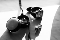 Black and white photo of watch and wedding rings lying on the ta Royalty Free Stock Photo