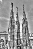 Black and white photo of the white marble statues of Cathedral Duomo di Milano on piazza, Milan cityscape Royalty Free Stock Photos