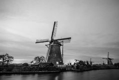 Black-white photo of windmills and water canal on sunset in Kinderdijk, Holland Royalty Free Stock Photos