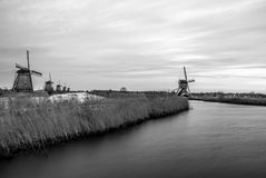 Black-white photo of windmills and water canal on sunset in Kinderdijk, Holland Stock Photo