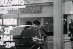 Black and white photo through the window of young lovely couple that kissing in the cafe stock photography