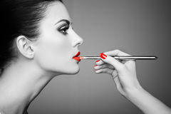 Black and white photo of woman painting lipstick. Beautiful woman face. Makeup detail. Beauty girl with perfect skin. Red lips and nails manicure royalty free stock photo