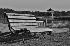 Black and white photo of wooden bench at the Alum Lake Kamencove jezero in Chomutov city in the foothills of the Krusne hory Mount. Ains in the Czech Republic Stock Images