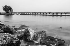 Black and white photo of the wooden bridge along the beach Royalty Free Stock Image