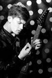 Black and white photo of young attractive rock musician playing electric guitar and singing. Royalty Free Stock Images
