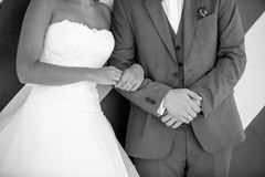 Black and white photo of young bride holding grooms hand Royalty Free Stock Image