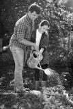Black and white photo of young father and daughter watering gard Royalty Free Stock Image
