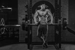 A black-and-white photo of a young handsome muscular weight-lifting bodybuilder, drinks sports after strong training, in the gym. royalty free stock photo