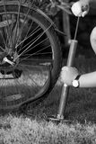 Black and white photo of young man pumping bicycle tyre with han Stock Photo