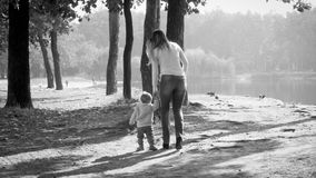 Black and white photo of young mother walking her toddler son in autumn park royalty free stock photography