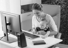 Black and white image of young owman sitting with her baby son behind computer desk at office. Black and white photo of young owman sitting with her baby son Stock Photo