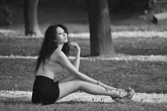 Black white photo young sexual woman with long legs and black hairl posing in nature Stock Photography