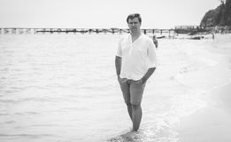 Black and white photo of young stylish man standing on the sea Royalty Free Stock Photo