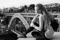 Black and white photo of young woman with dreadlocks sitting on the background of the Dom Luis I bridge in Porto Royalty Free Stock Photos