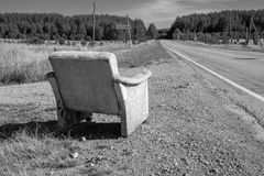 Black and white photograph of a chair which is along the road for those who will wait for the car. An old chair on the road stock photography
