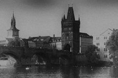 Black-and-white photograph of the Charles bridge. Prague`s historical center. Photo from the river. Quay and buildings of European cities royalty free stock photo