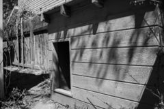Lonely Doghouse. Black and white photograph of an empty doghouse royalty free stock photos
