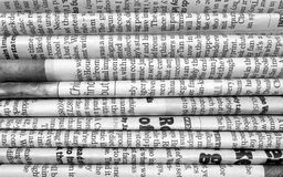 Stack of Newspapers. A black and white photograph of English Language newspapers folded and stacked to provide a background Royalty Free Stock Photo