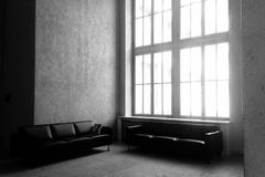 Minimalist Living Space with Couches. A black and white photograph of a large minimalist living room with big window Stock Image