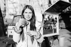 Black and white photography of beatiful young woman with a cup of hot drink outdoors Royalty Free Stock Image